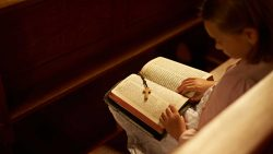 A little girl kneeling with a Bible.