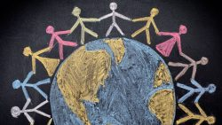 Chalk illustration of people holding hands around the world